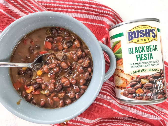 A grey bowl filled with beans next to a can of beans.