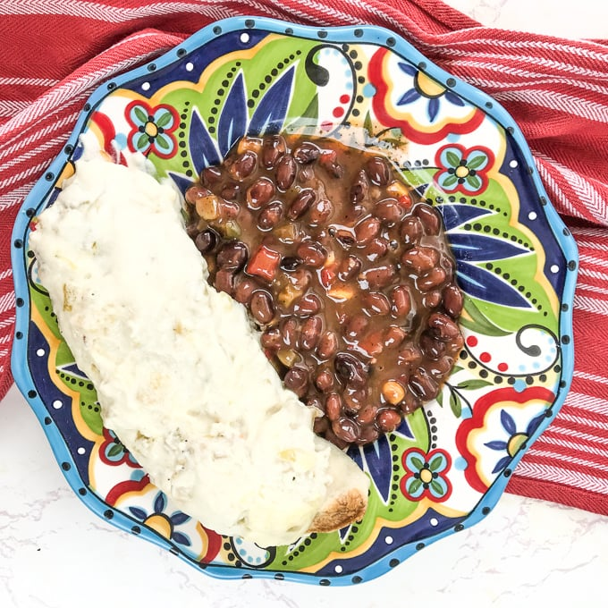 A plate of white chicken enchiladas and black beans.