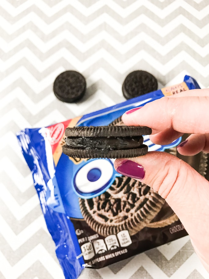 A hand holding an OREO sideways so the filling is shown.