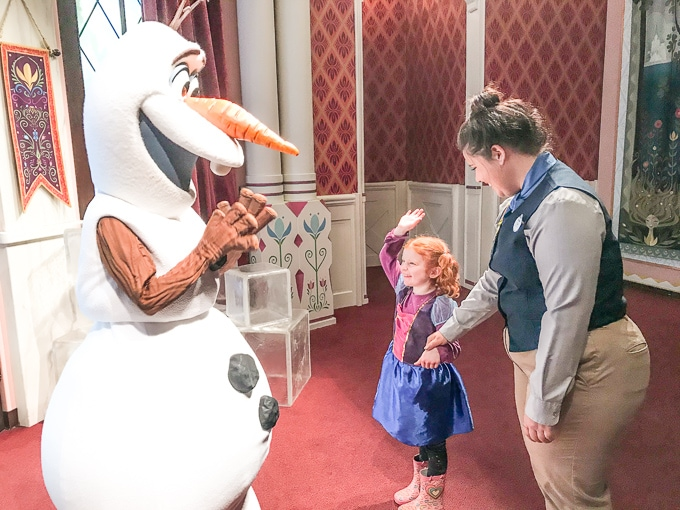 A little girl giving Olaf a high five during her trip to Disneyland in Winter.