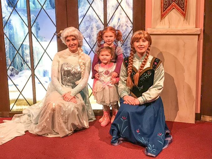 Two little girls standing next to Anna and Elsa from Frozen at California Adventure in Winter.