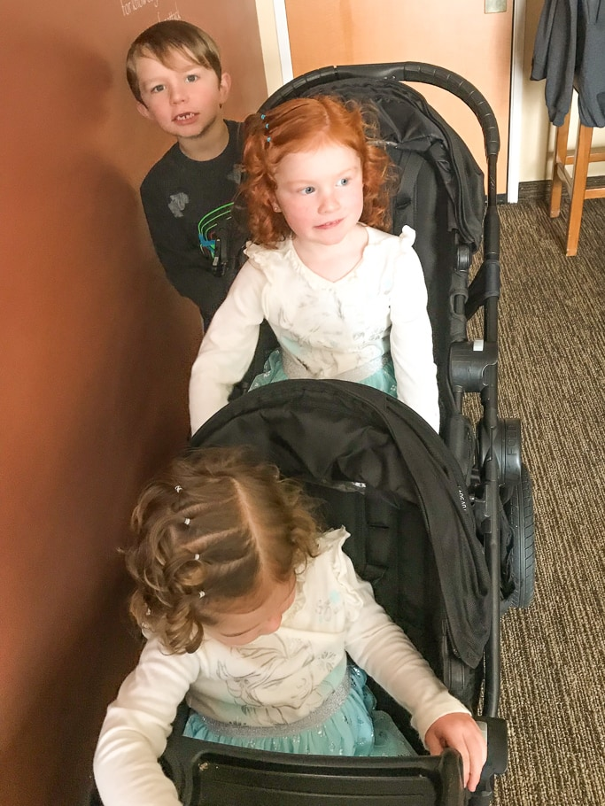 Three kids riding on a City Select Double stroller (with glider board) during a trip to Disneyland in Winter.