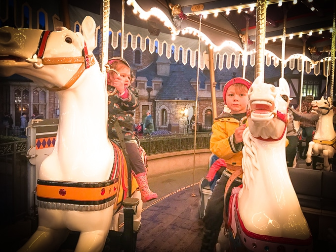 Two kids on the Carousel at Disneyland in Winter.