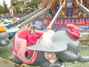 A little girl riding the Dumbo ride at Disneyland in Winter.