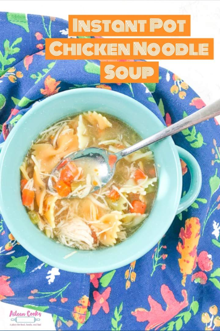 Instant pot chicken noodle soup in a turquoise bowl and on top of a blue floral dish towel.