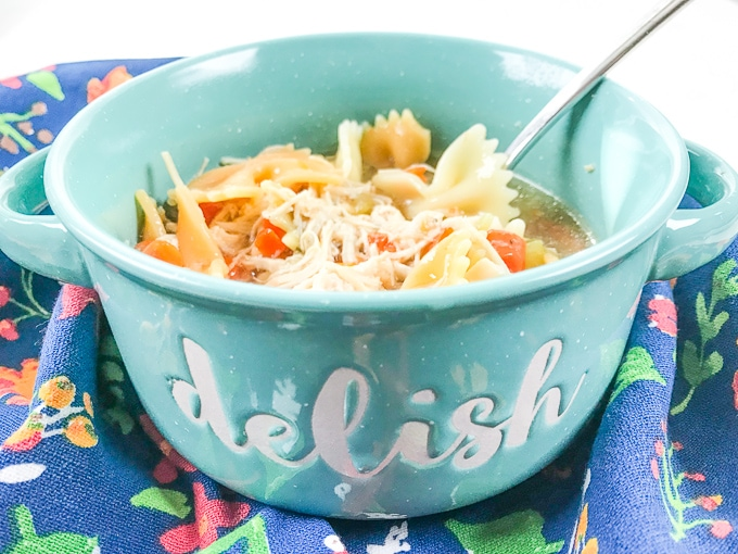 """A teal bowl with the words """"delish"""" written on the front and filled with the instant pot chicken noodle soup recipe."""