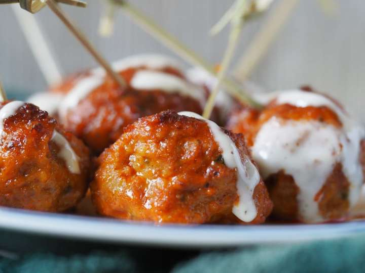 A close up of buffalo meatballs with toothpicks sticking out of the otp.