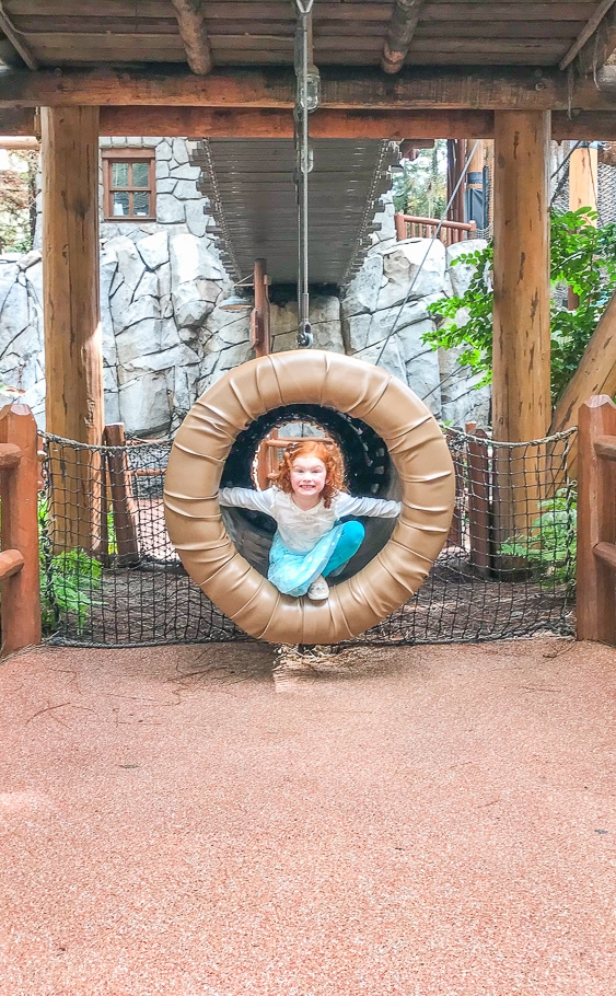 A little girl poking her head out of the tunnel at the Redwood Creek Challenge Trail inside Disney California Adventure Park.
