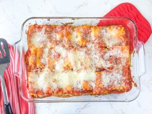 A casserole dish filled with spinach lasagna roll-ups recipe on top of a red oven mitt.