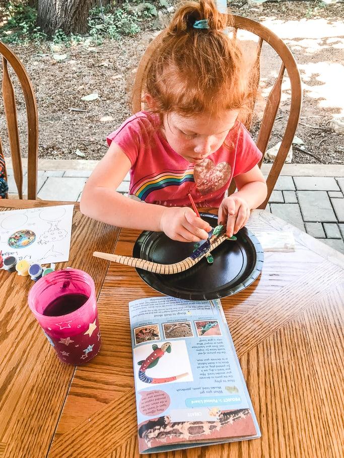 A little girl painting a wooden lizard.
