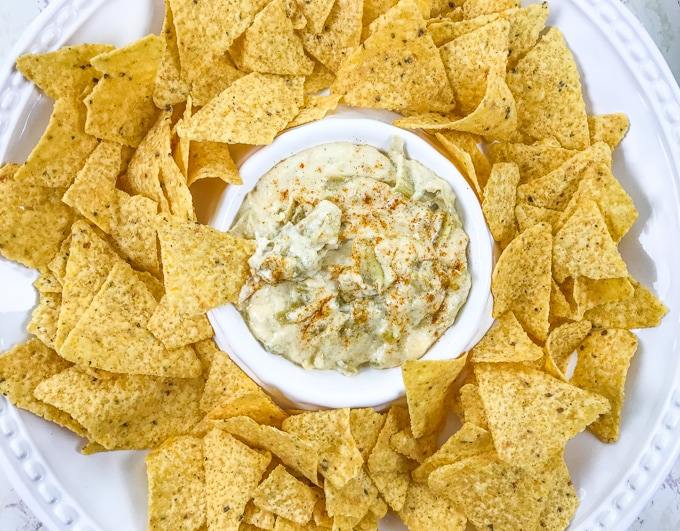 A chip and dip platter with instant pot artichoke dip in the center and surrounded by chips.