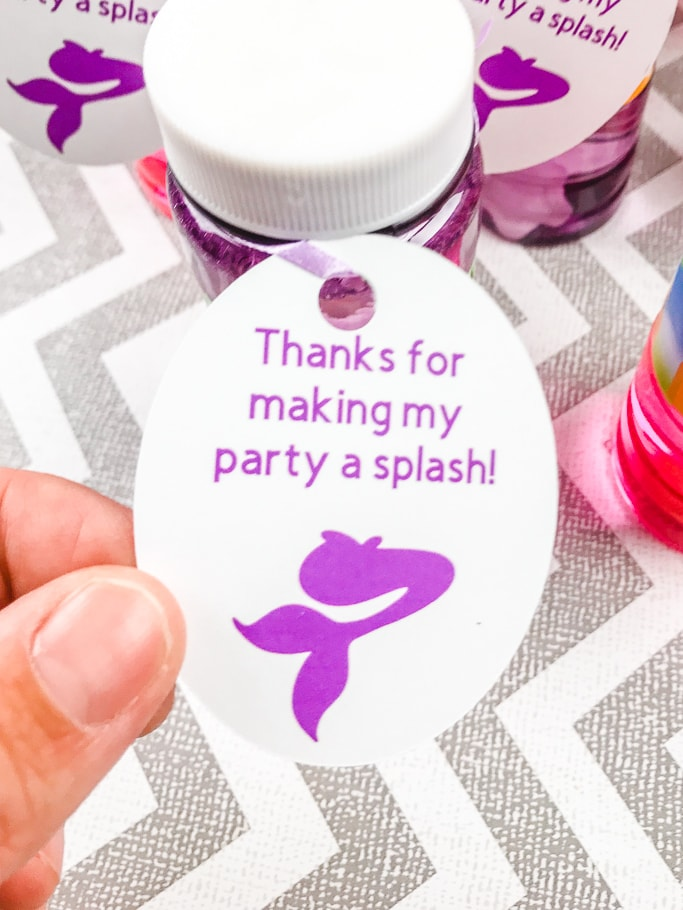 A hand holding on to a mermaid favor tag attached to a bottle of bubbles.