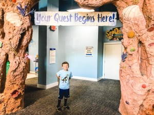 """A boy posing in front of a sign that says """"Your Adventure Starts Here""""."""
