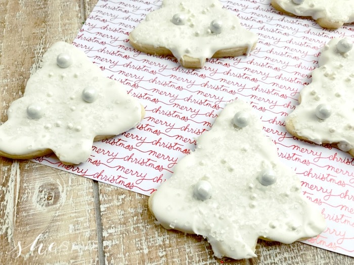 White chocolate Christmas tree cookies on a red and white towel.