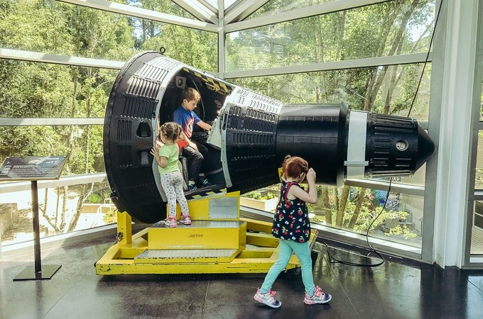 Kids climbing inside a rocket ship at Chabot Space and Science Center.