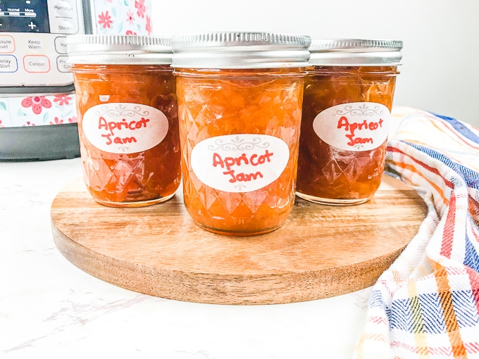 Three jars of apricot jam on a wooden platform.