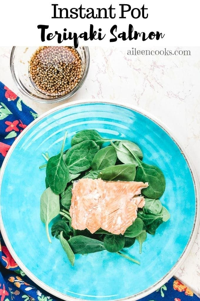 instant pot salmon on a blue plate next to a glass blow of homemade teriyaki sauce.