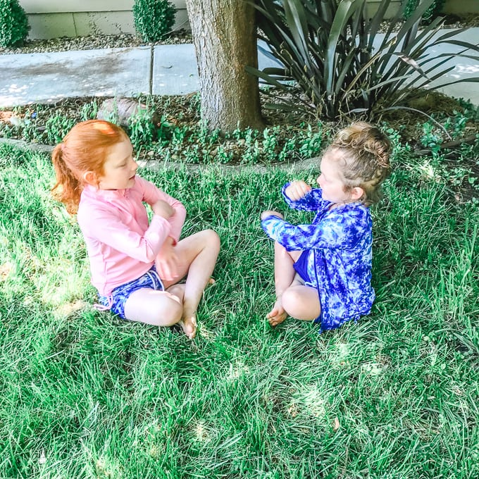 Two girls sitting on grass in their swimsuits, playing pat-a-cake.