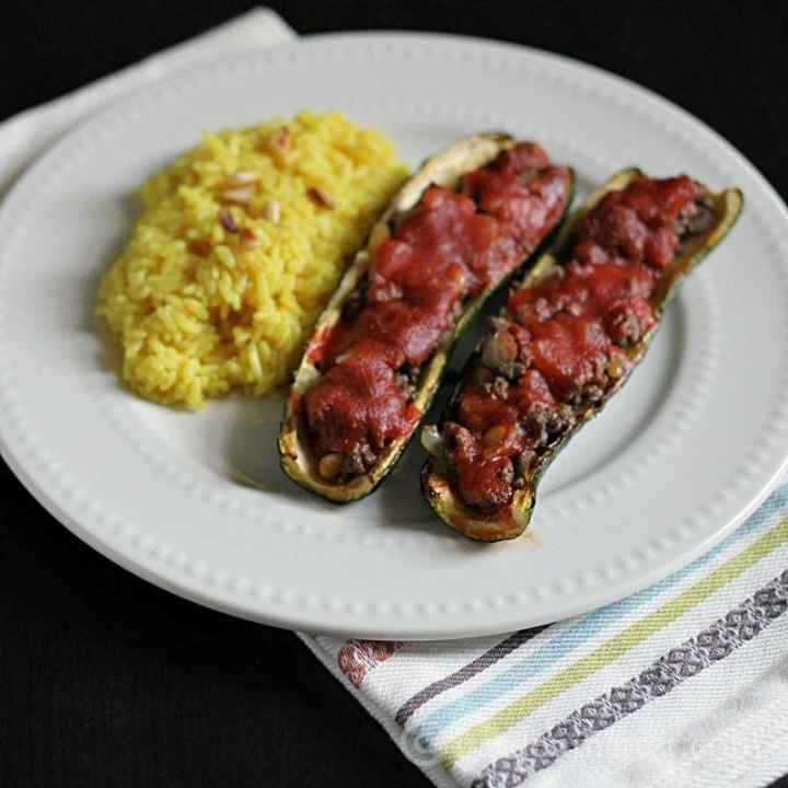 Two pieces of stuffed zucchini on a white plate.