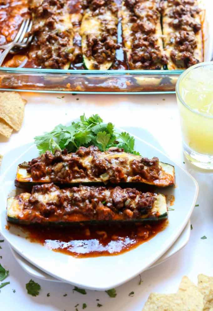 Two enchilada zucchini boats on a white plate in front of a glass baking dish.