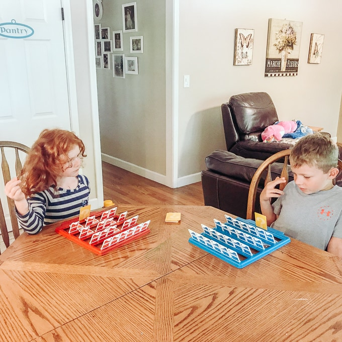 Two kids playing Guess Who? together.