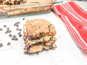 Chocolate chip cookie cheesecake bars stacked up in front of pan of bars.