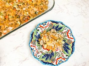 A casserole dish filled with turkey noodle casserole next to a colorful plate with a serving of turkey and noodle casserole.