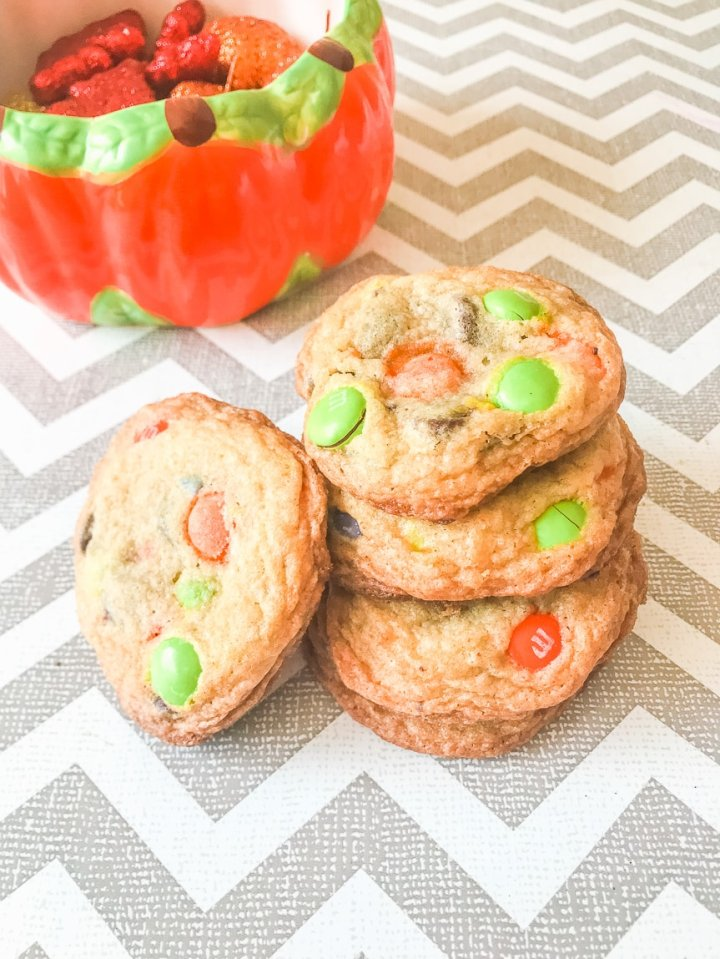 A stack of three halloween M&M cookies with one cookie leaning on the tower of cookies.