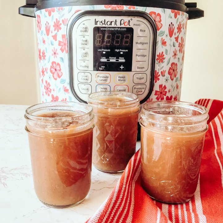 Three jars of instant pot apple butter in front of a pressure cooker.