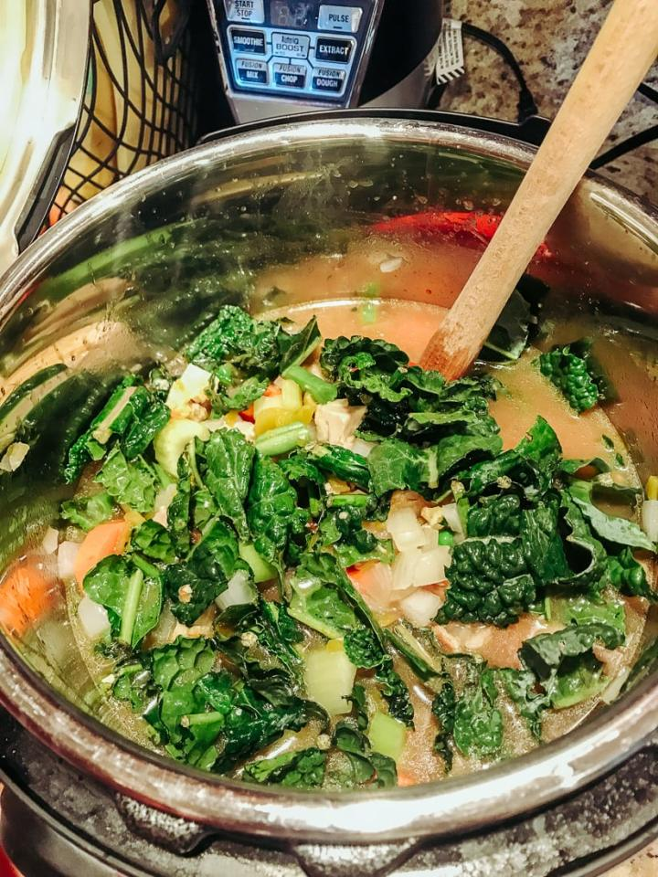 Chicken broth, vegetables, and chicken being stirred for instant pot chicken vegetable soup.