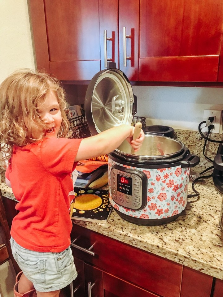 Little girl stirring onion and garlic in an instant pot.