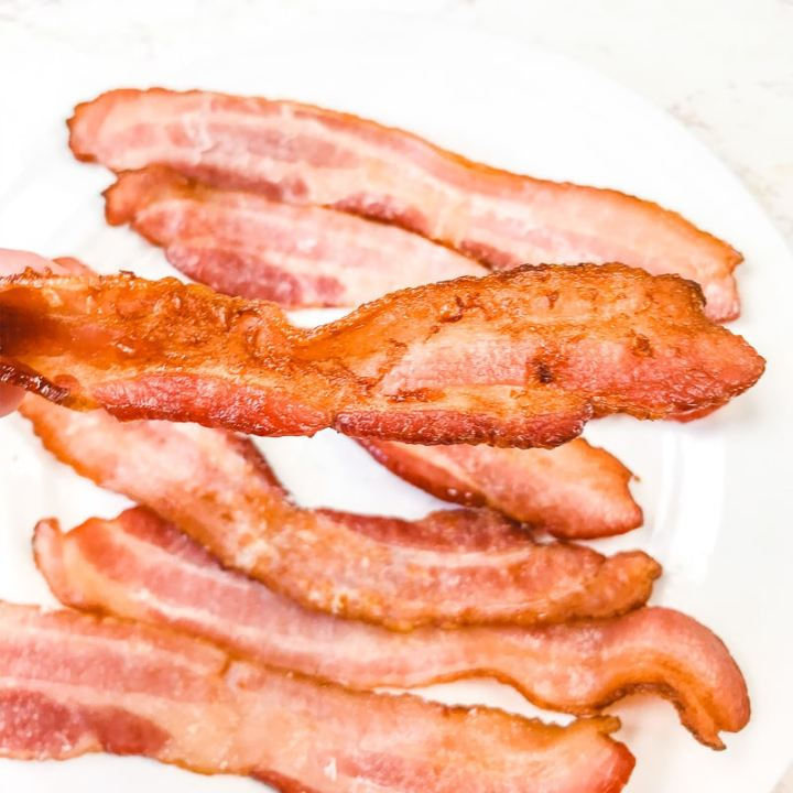 A slice of extra crispy air fryer bacon being held in front of a plate of bacon.