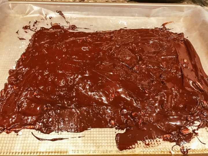 Melted semi sweet chocolate spread over crushed candy canes on a cookie sheet.