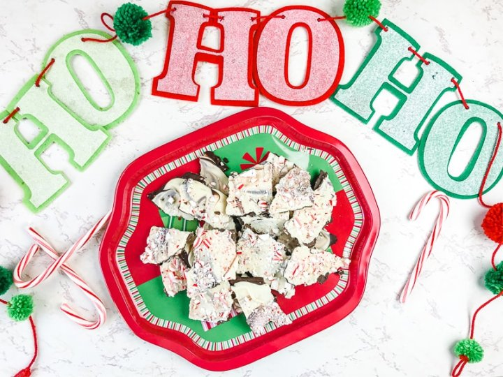 """A holiday platter filled with peppermint bark surrounded by candy canes and a banner that says """"ho-ho-ho""""."""