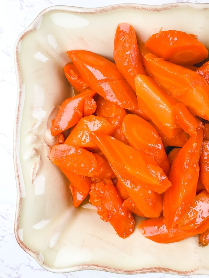 A side view of instant pot carrots in a cream colored serving dish.