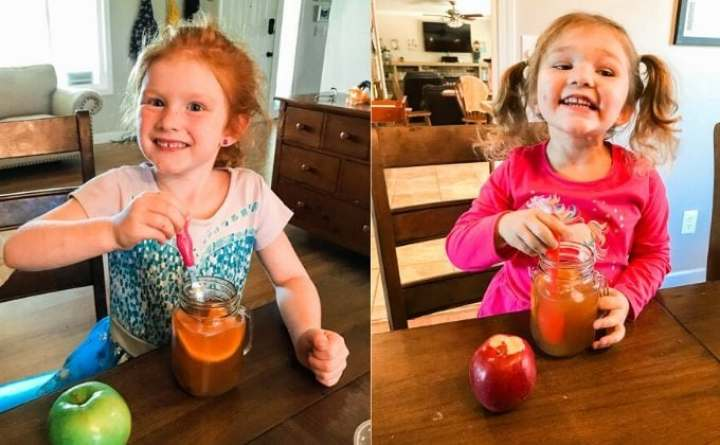 Two girls sitting at a table smiling and drinking instant pot apple cider.