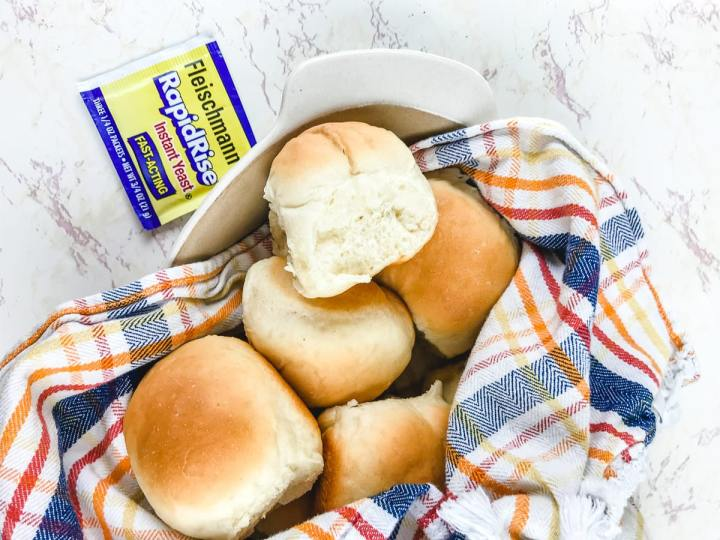 A white dish holding a pile of Parker house rolls.