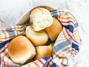 A basket filled with warm Parker house rolls.