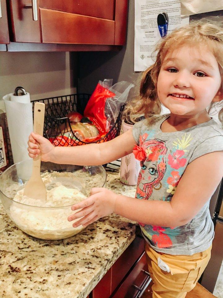 Little girl mixing pumpkin cornbread muffin batter.