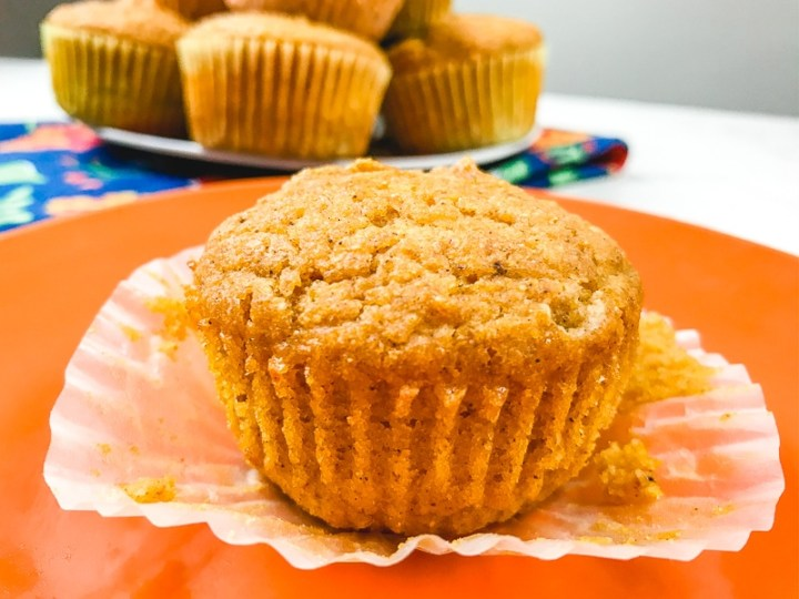 A pumpkin cornbread muffin on an orange plate with the liner peeled off to show the lines of the pumpkin muffin underneath.