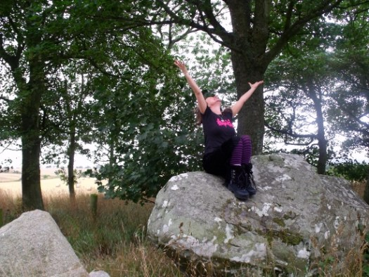 Author Ailish Sinclair reaching for the skies at Berrybrae Stone Circle in Aberdeenshire