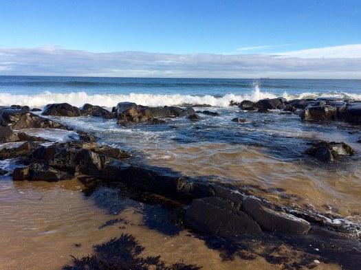 waves crash at St Combs beach