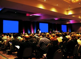 Audience members listening to a medical presentation at a conference