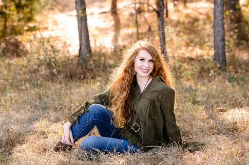 Smiling Redhead Senior Portrait in woodland setting