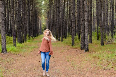 girl in jeans dances in the woods portrait