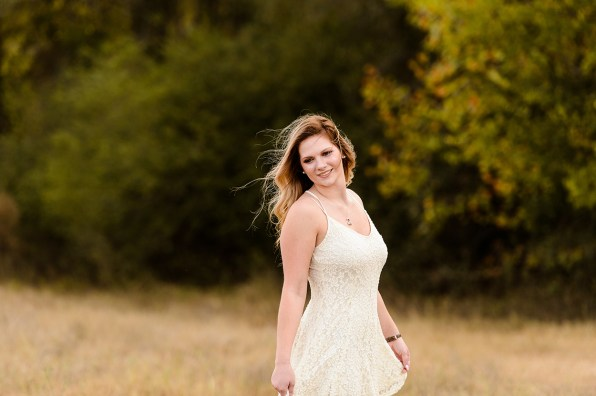 Young girl in white dress poses for senior portrait
