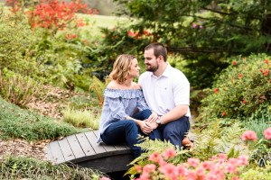 middle georgia engagement session tryphenas garden couple sitting on bride over water in flower garden
