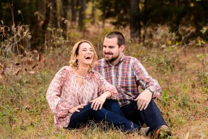couple laughing in field during engagement session middle georgia