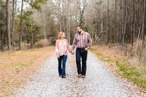 couple walking on gravel road in middle georgia for engagement session
