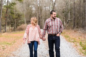 couple in pink walking on gravel road engagement session